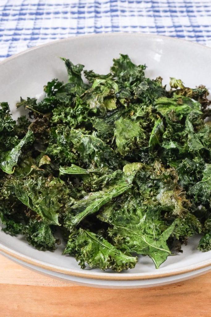 crispy kale chips in bowl on wooden board
