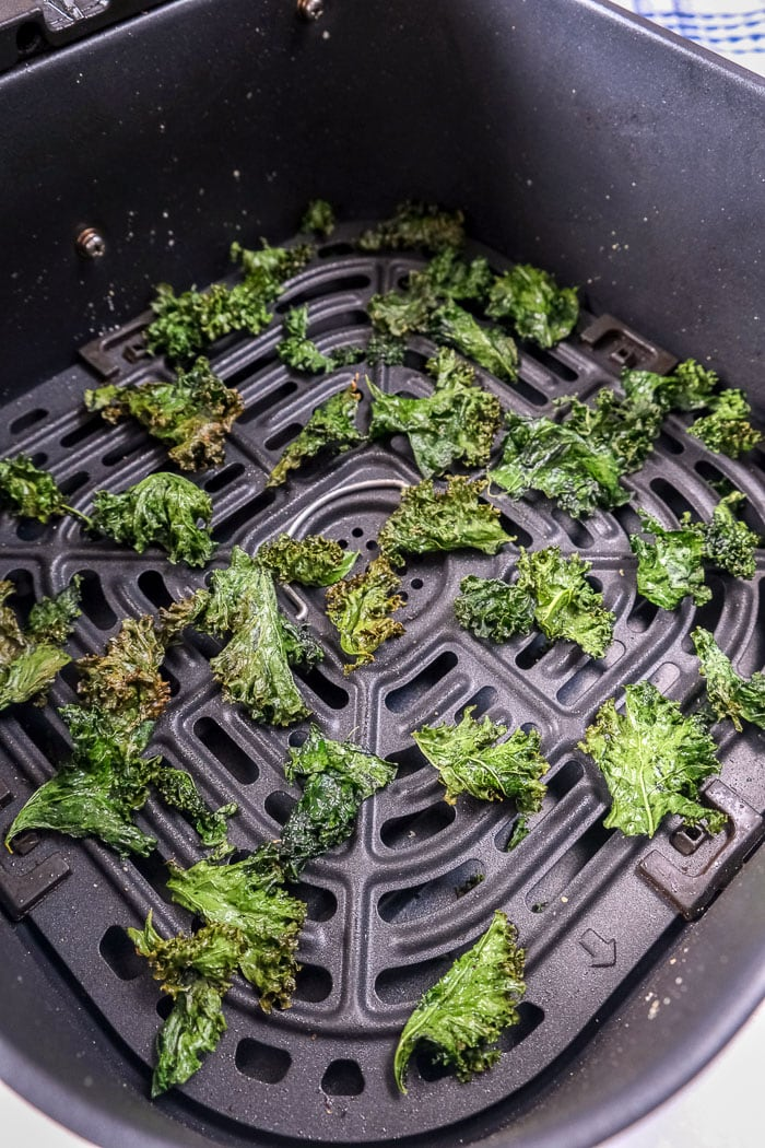 crispy kale chips in black air fryer tray on counter