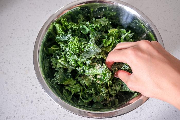 hand massaging raw kale in metallic bowl on counter