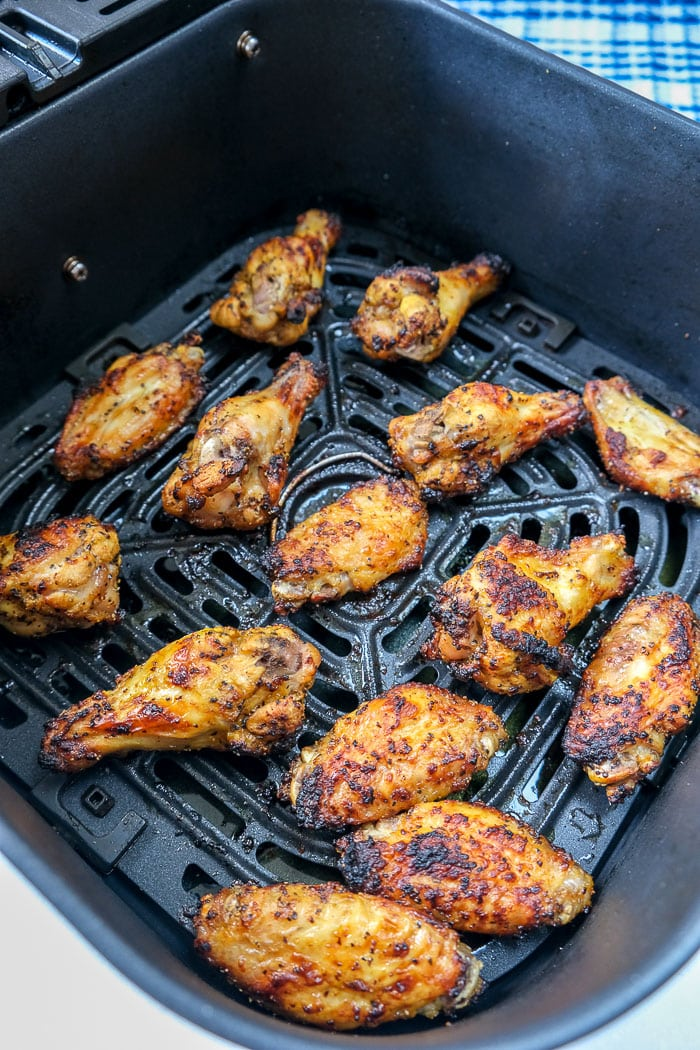 cooked chicken wings in black air fryer tray on counter