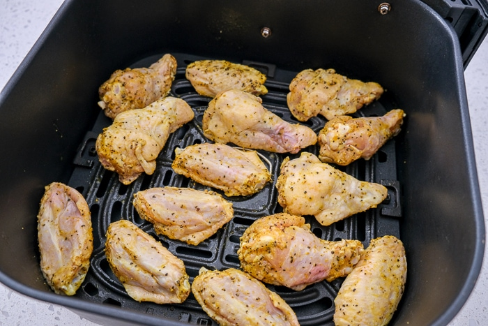 raw chicken wings in black air fryer tray