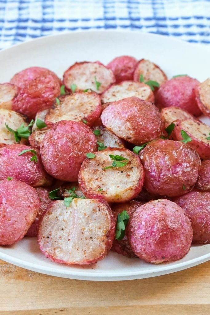 cooked radishes on white plate with chopped parsley