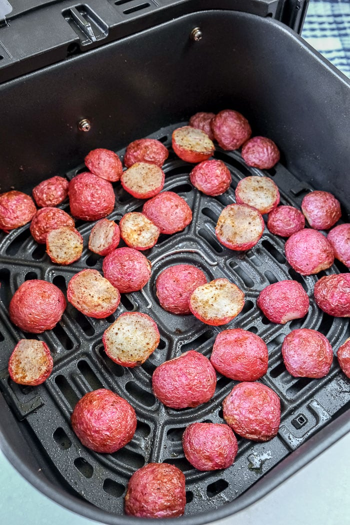 cooked radishes in black air fryer tray on counter top