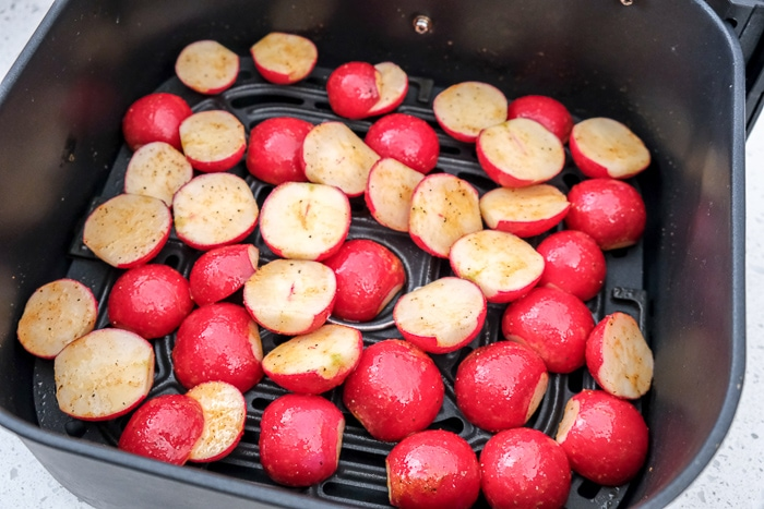 raw radishes in black air fryer tray on counter