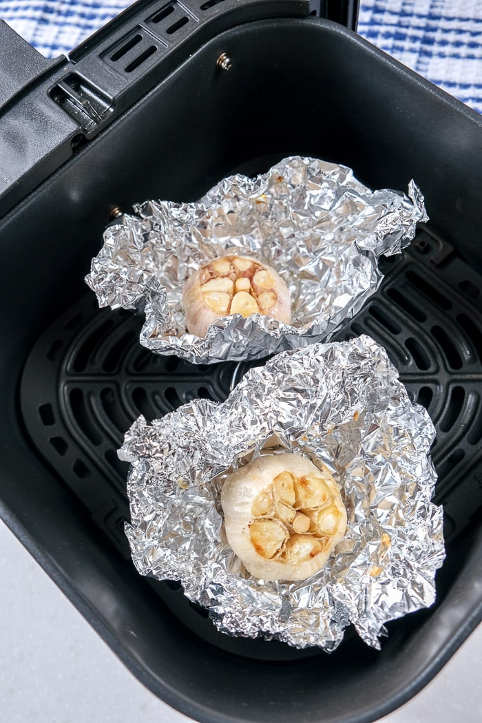 roasted garlic in tin foil packages in black air fryer tray