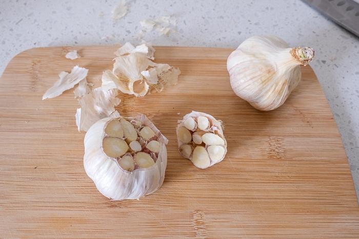 garlic bulb with top cut off on wooden cutting board