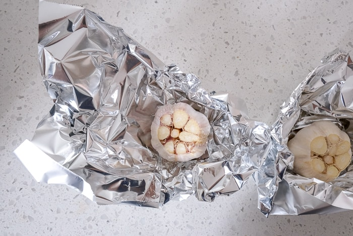 raw garlic bulbs in pieces of tin foil on white counter top