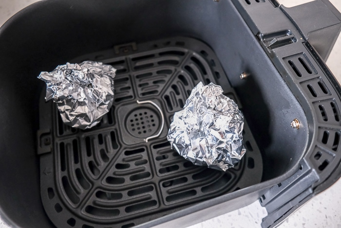garlic bulbs wrapped in tin foil in black air fryer tray