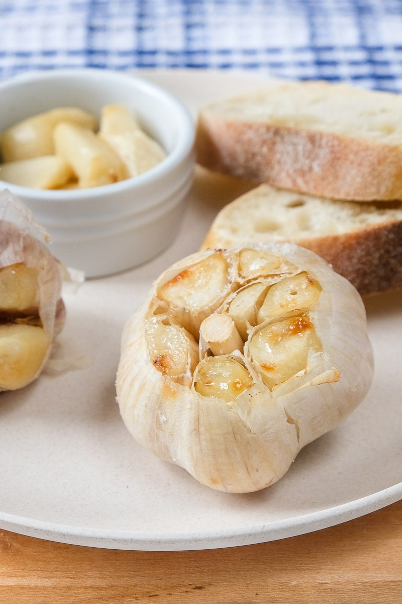 roasted garlic bulbs on white plate with bread behind