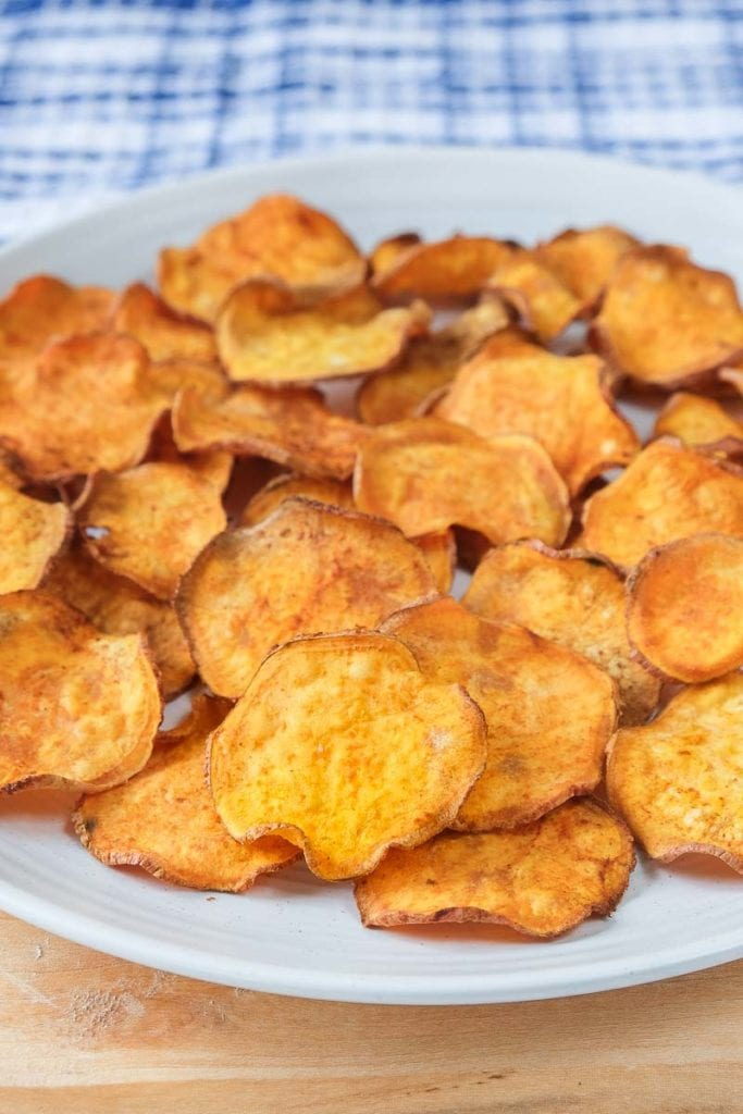 sweet potato chips on white plate with blue cloth behind