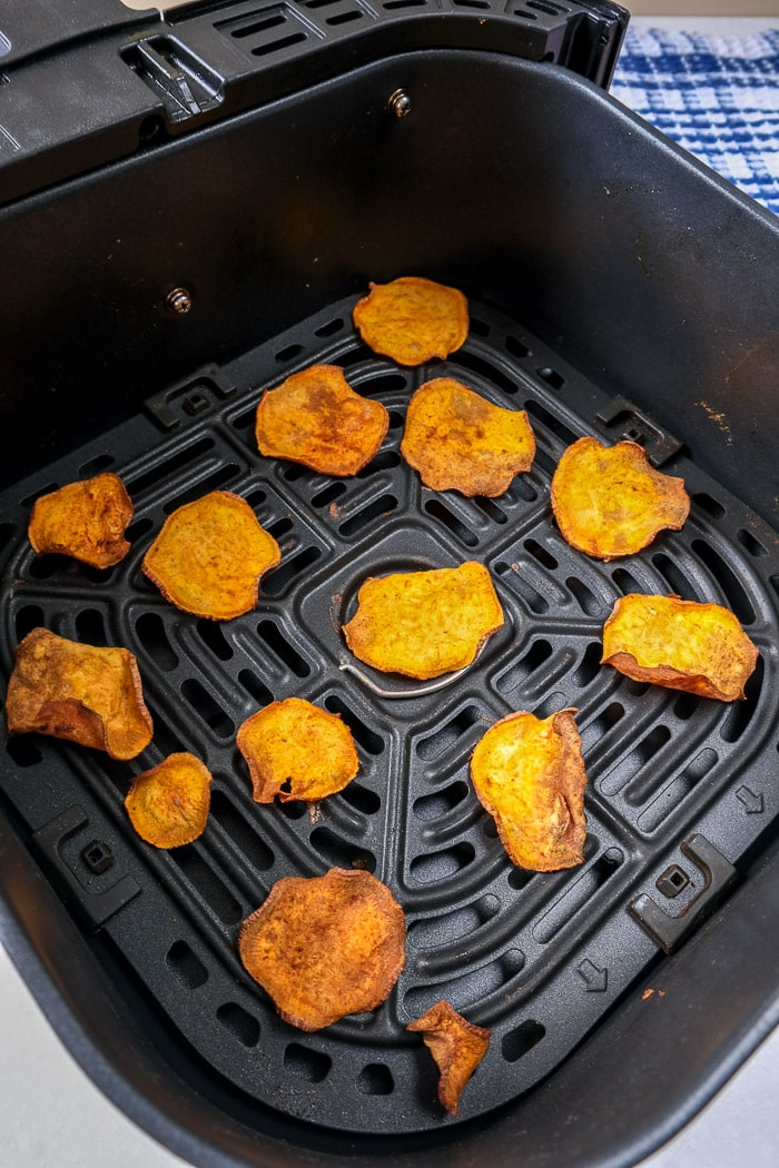 crispy sweet potato chips in black air fryer tray on counter top