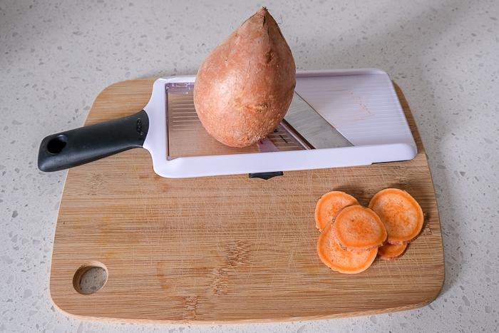 sweet potato sitting on mandolin on wooden cutting board