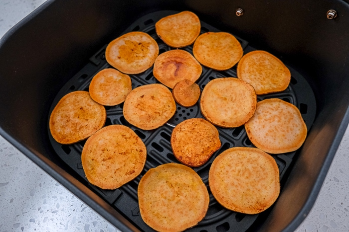 sweet potato chips in black air fryer tray on counter