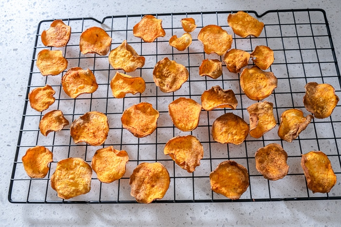 sweet potato chips sitting on black cooling rack on counter top