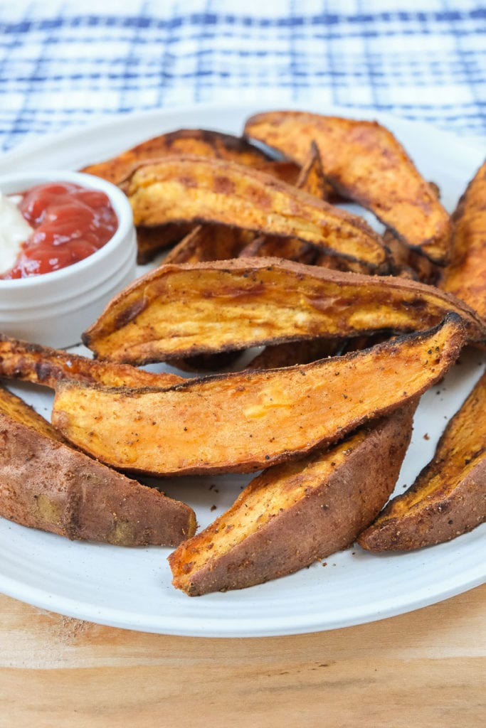 crispy sweet potato wedges on white plate with dipping sauce behind
