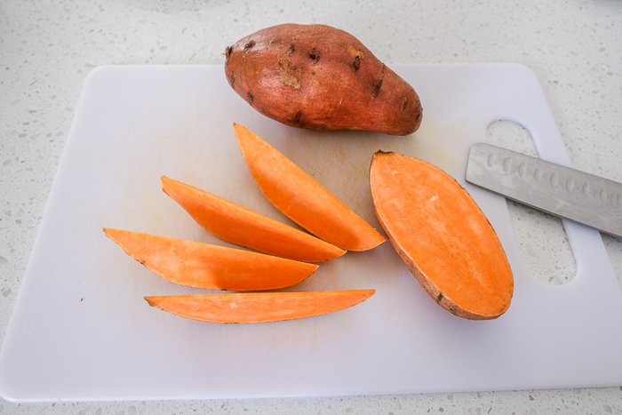 raw sweet potato cut into wedges on white cutting board