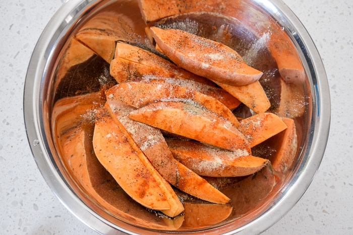 raw sweet potato wedges in silver mixing bowl on white counter