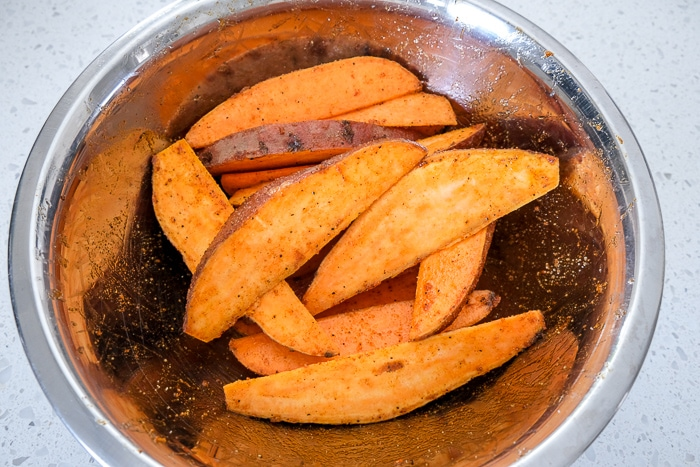 raw sweet potato wedges covered in oil and spices in silver bowl on counter