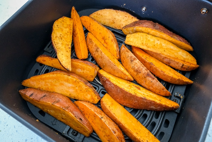 uncooked sweet potato wedges in black air fryer tray