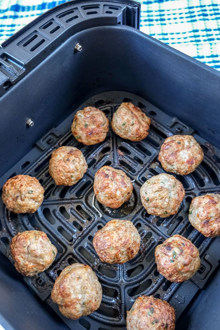 cooked turkey meatballs in black air fryer tray
