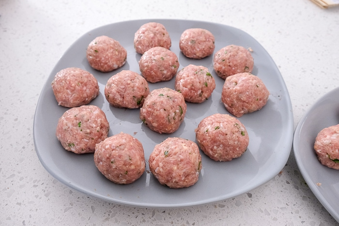 formed raw turkey meatballs on grey plate on white counter top