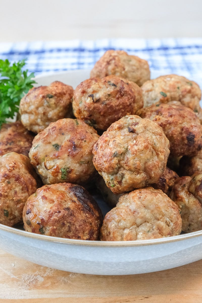 cooked turkey meatballs in bowl on wooden board