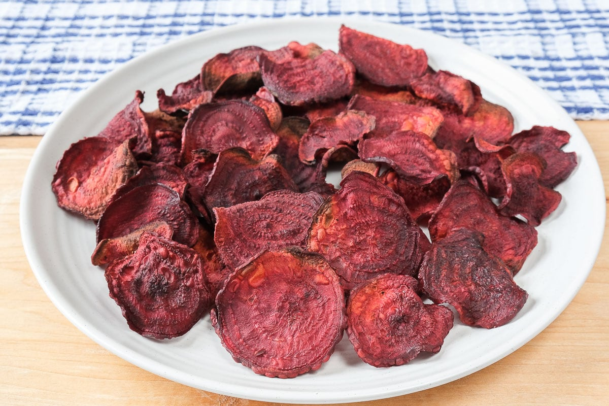 air fried beet chips on white plate with wood underneath