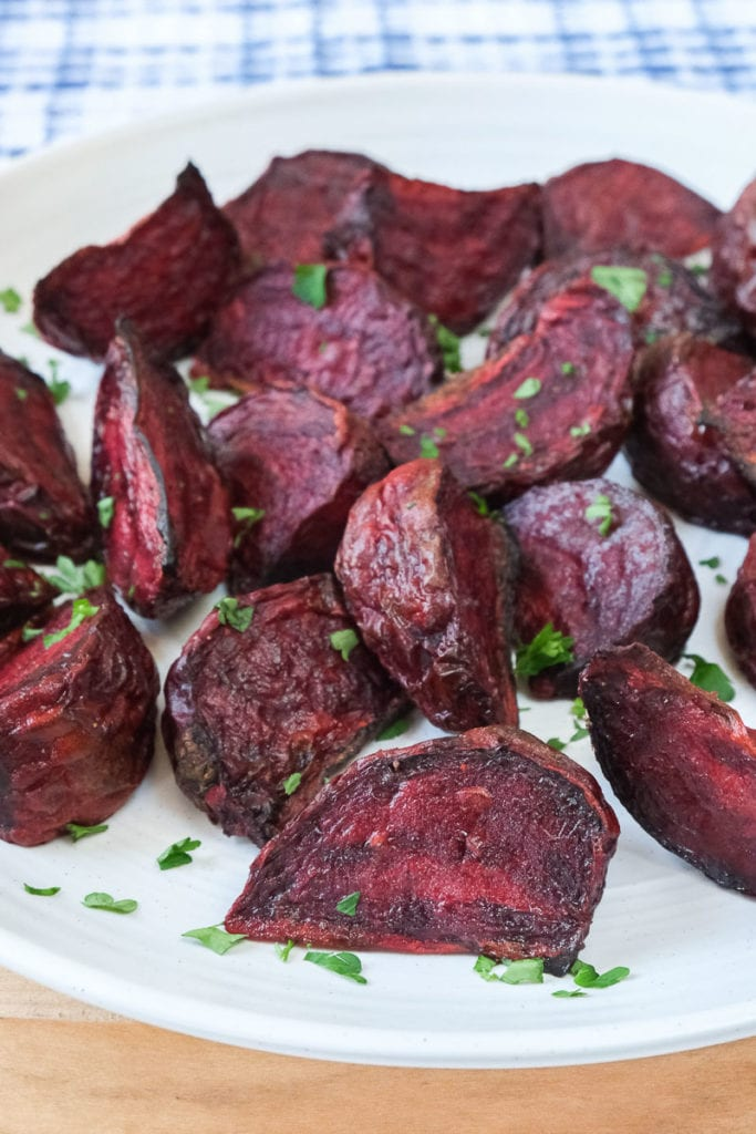 cooked beets on white plate with parsley