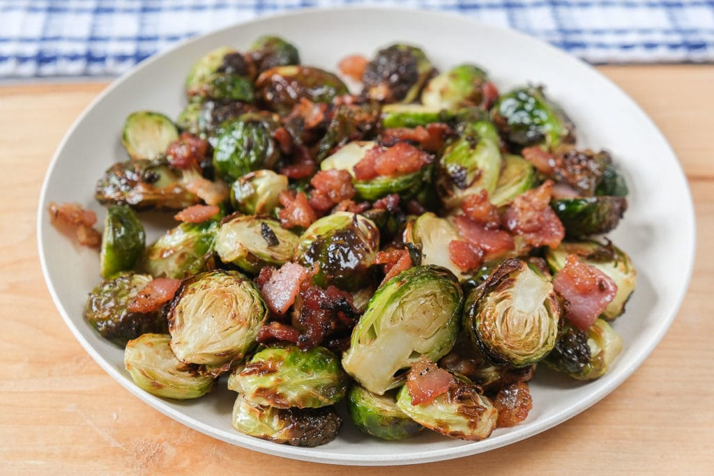 brussels sprouts on white plate with bacon on wooden board
