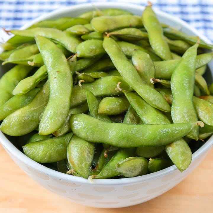 bowl of green edamame on wooden board with blue cloth behind