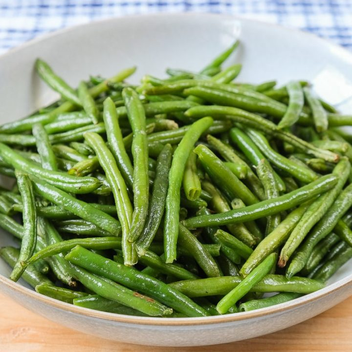 green beans in bowl on wooden board