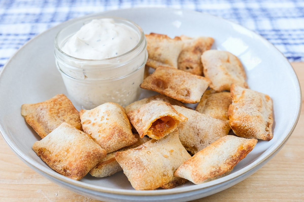 cooked pizza bites in bowl with dipping sauce behind