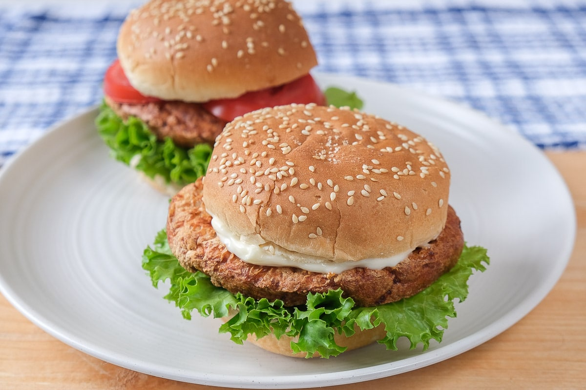 two turkey burgers with buns on white plate on wooden board