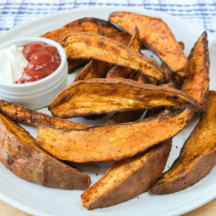 sweet potato wedges on white plate with dipping sauce in dish beside