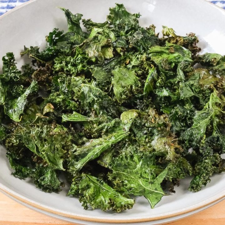 bowl full of green kale chips on wooden board