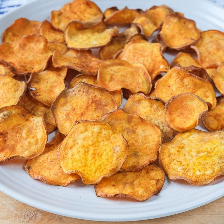 sweet potato chips on white plate with wood underneath