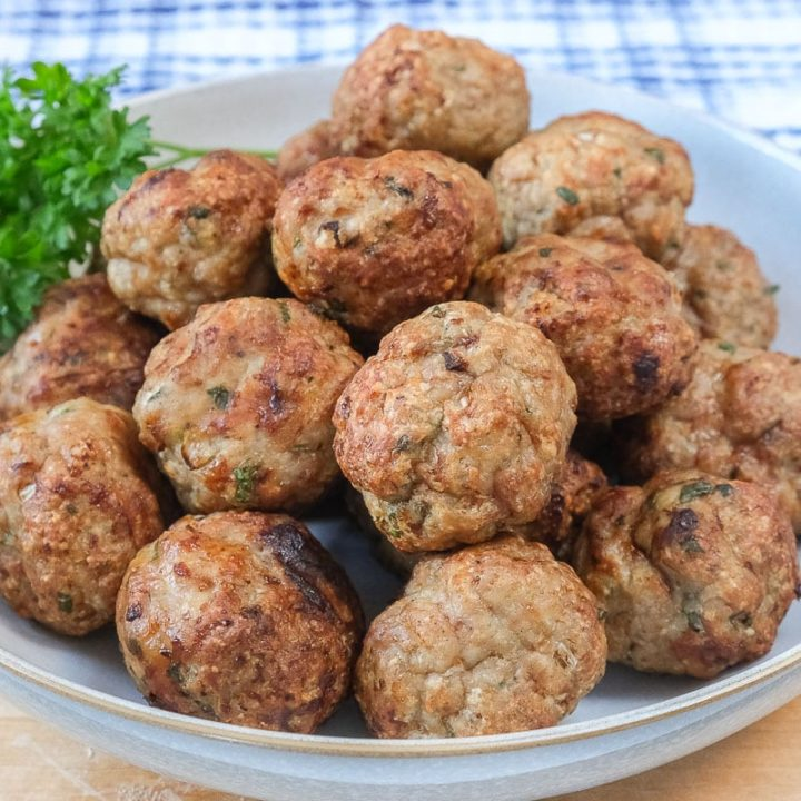 turkey meatballs in bowl on wood with parsley beside