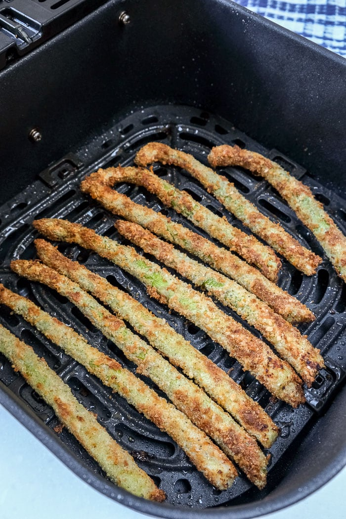 cooked breaded asparagus stalks in black air fryer tray on counter