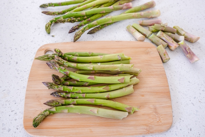 green asparagus with ends trimmed on wooden cutting board on counter