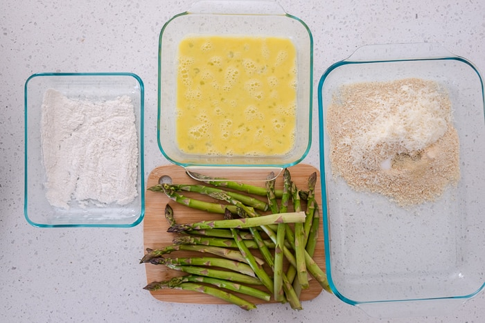 dishes with egg breadcrumbs and flour for breading asparagus on white counter