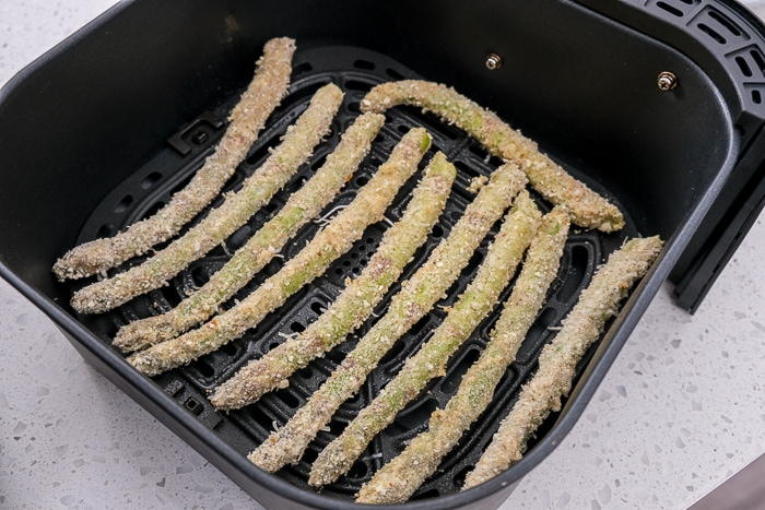 stalks of breaded asparagus in black air fryer tray on white counter