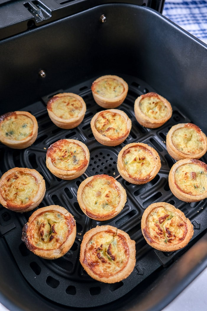 cooked mini quiche in black air fryer tray on counter