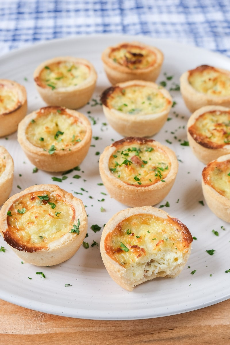 cooked mini quiche with bite out of it on white plate