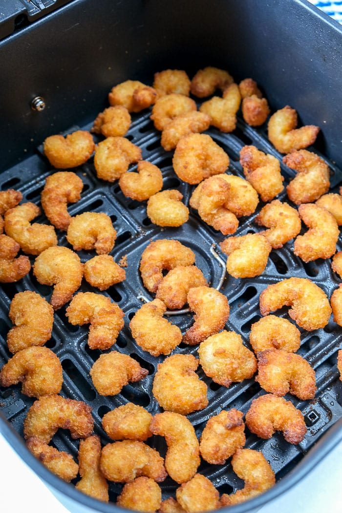 cooked breaded shrimp in black air fryer tray