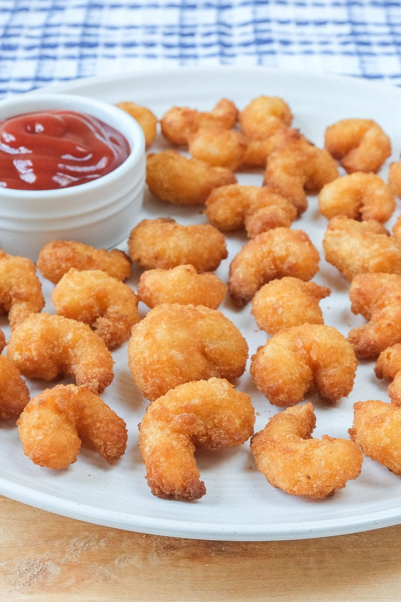 breaded popcorn shrimp on plate on wooden board with ketchup behind