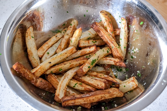 fresh fries tossed in cheese and spices in silver mixing bowl