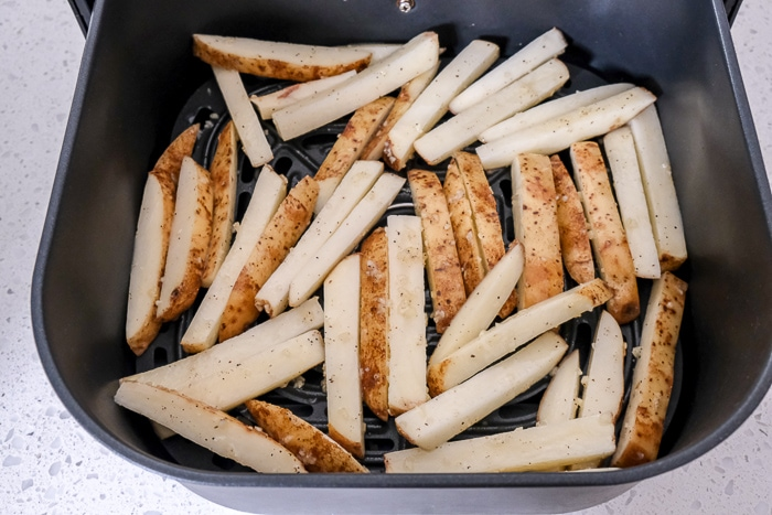 raw fries in black air fryer tray on white counter