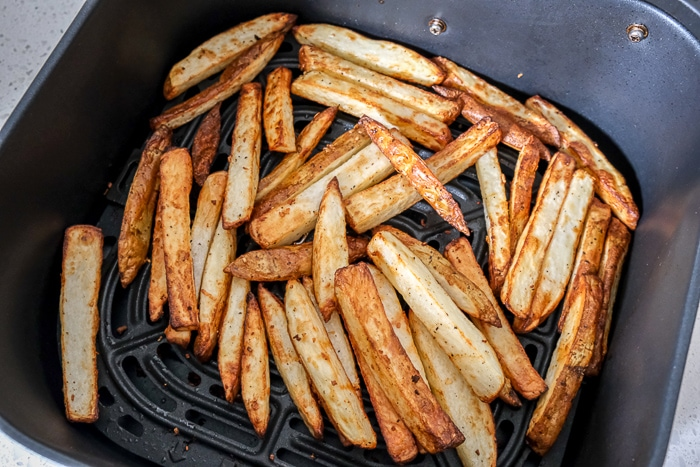 cooked fries in black air fryer tray on counter top