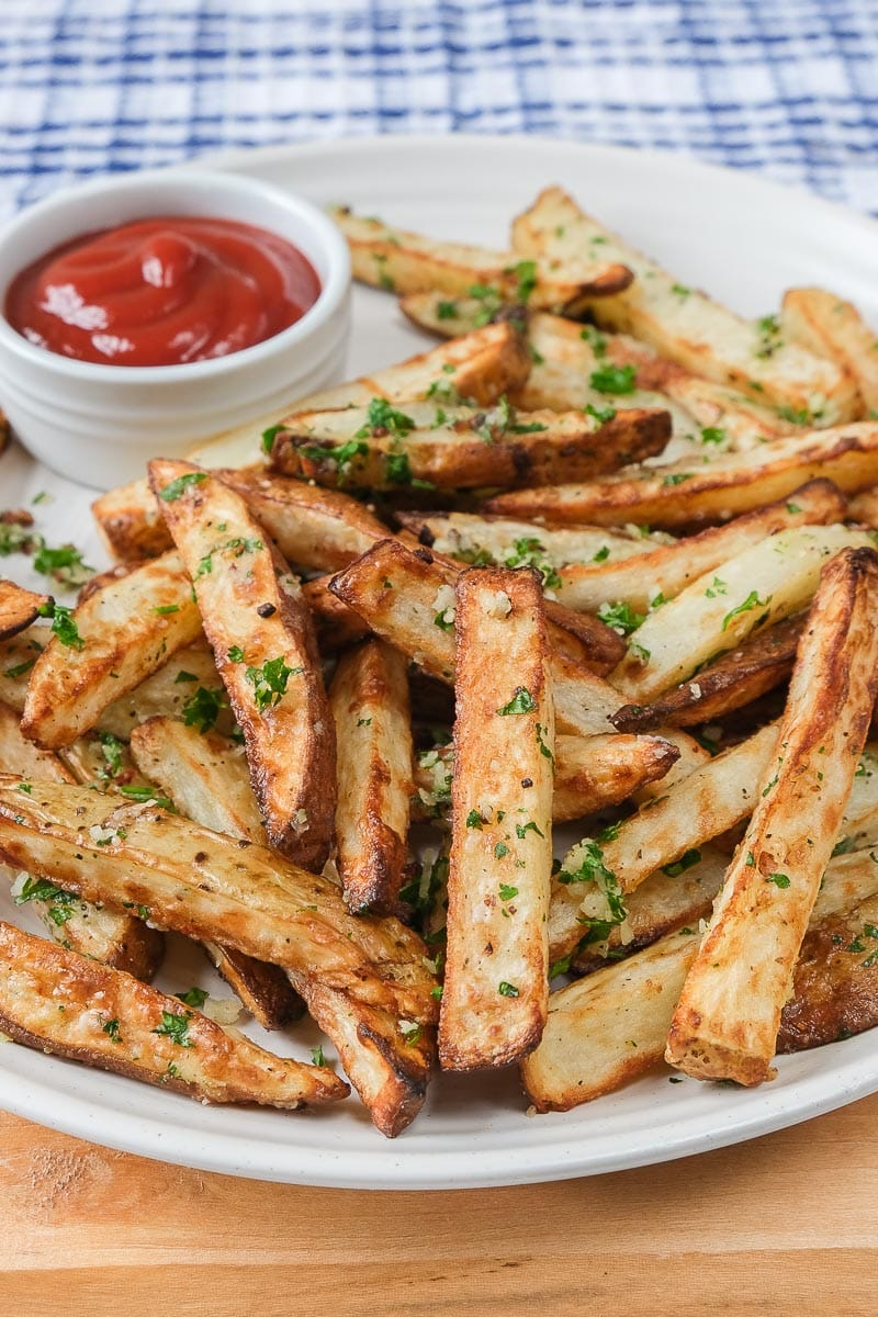 garlic cheesy fries on white plate with ketchup dipping bowl behind