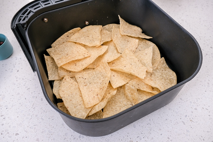 black air fryer tray lined with tortilla chips on white counter